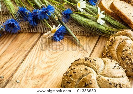Whole Wheat Rye Bread Rolls With Ears Of Cereal And Cornflowers Located On Wood Background. Rustic A