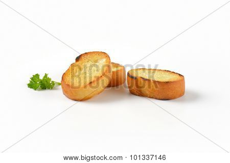 three fried bread slices (croutons) on white background