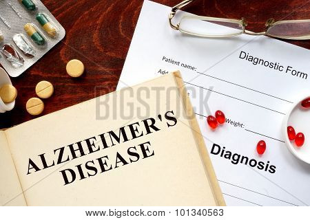 Alzheimers disease written on book with tablets.