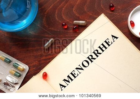 Amenorrhea written on book with tablets.