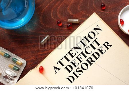 attention deficit disorder written on book with tablets.