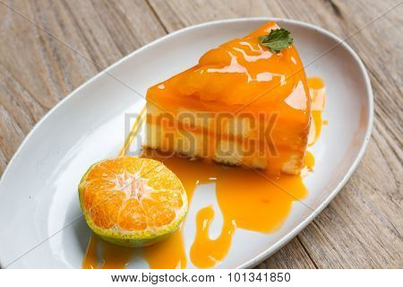 orange cake with orange topping in white dish