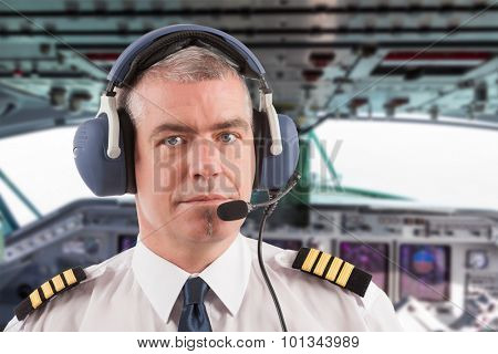 Airline pilot wearing uniform with epaulettes and headset, on board passenger aircraft.