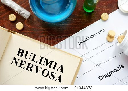 bulimia nervosa written on book with tablets.