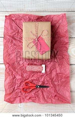 Overhead view of a Christmas present wrapped in plain brown paper, a spool of string and scissors on a sheet of crumpled red tissue paper. The objects are on a rustic whitewashed wood table.