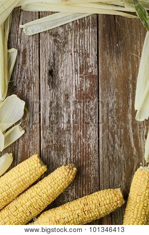 Corn With Corn Husk Surrounding Rustic Wooden Table Sample Text