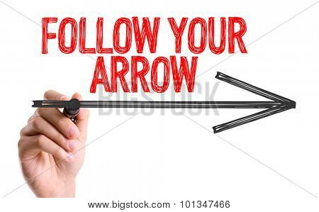 Hand with marker writing the word Follow Your Arrow