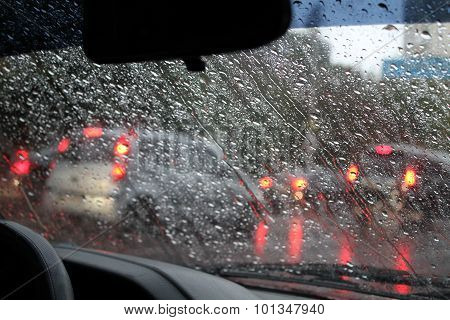 Water drops on car windshield on street at rain