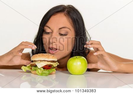 a young woman can not decide between a hamburger and an apple itself. healthy or unhealthy diet.