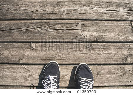 First persn perspective of wooden boardwalk and shoes