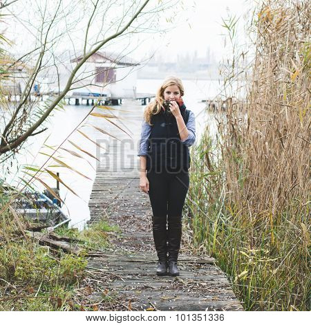 Happy free blonde woman enjoying fresh air at lakeside. Autumn concept.