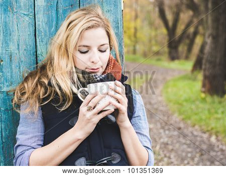 Autumn woman drinking coffee. Fall concept of young woman enjoying hot beverages over blue wooden wall. Caucasian female model in city forest park.