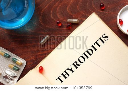 Thyroiditis written on book with tablets.
