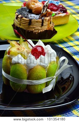 Delicious Green Cake With Cherry And Carambola On Black Plate