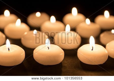 Group Of Burning Candles At A Black Background