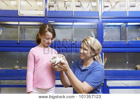 Sales Assistant Showing Girl Guinea Pig In Pet Store