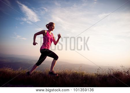 Beautiful Young Woman Runs Cross Country On A Mountian Path At Sunrise