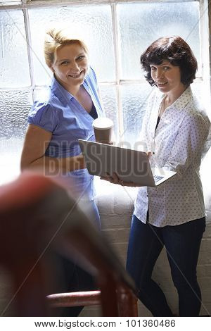 Two Businesswomen With Laptop Having Informal Meeting In Office