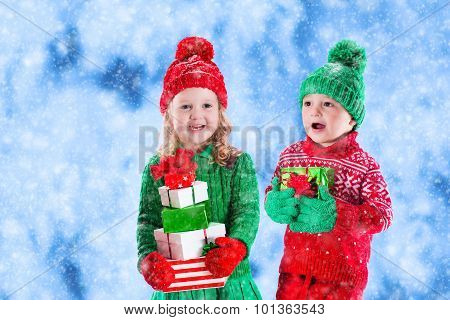 Kids With Christmas Presents In Winter Park In Snow