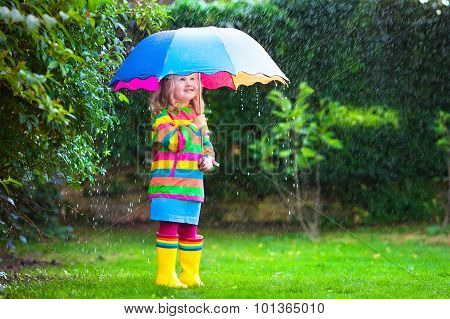 Little Girl With Colorful Umbrella Playing In The Rain.