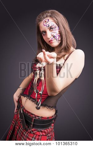 Face Art Concept: Portrait Of Sexy Brunette Woman In Corset Holding And Demonstrating Handcuffs. Fac
