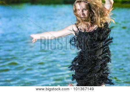 Lifestyle Concept: Portrait Of Happy Smiling Woman Making A High Jump Near Water Shore