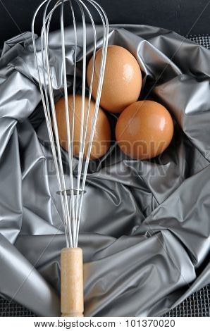 Whisk In Front Of Eggs On Silver Texture