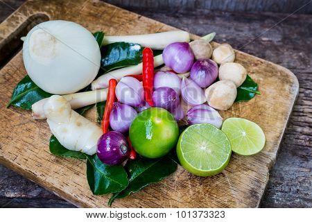 Kaffir Lime Leaf, Lemon, Lemongrass, Galangal, Chili, Onions And Straw Mushroom Over Chopping Block