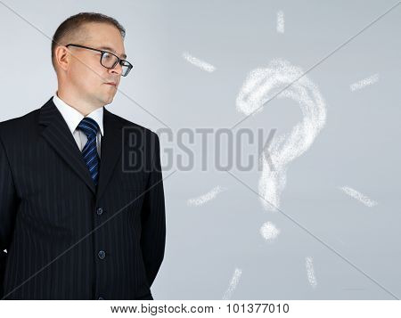Businessman Is Thinking And Looking At Chalk Drawn Question Mark Over Gray Background