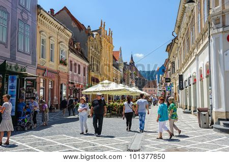 Brasov, Transylvania, Romania, 6th July 2015: Republic street is par of pedestrian area in historical center of city, people walkinng and sitting at outdoor terraces and restaurants.