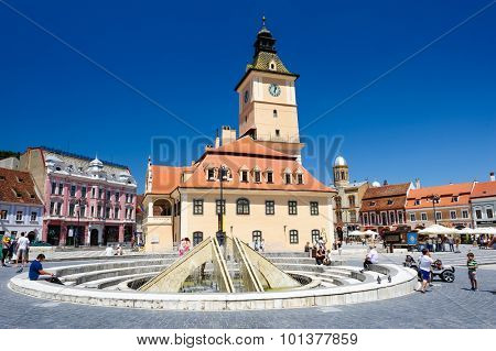 Brasov, Transylvania, Romania, 6th July 2015: Brasov Council Square is historical center of city, people walkinng and sitting at fountain, outdoor terraces and restaurants.