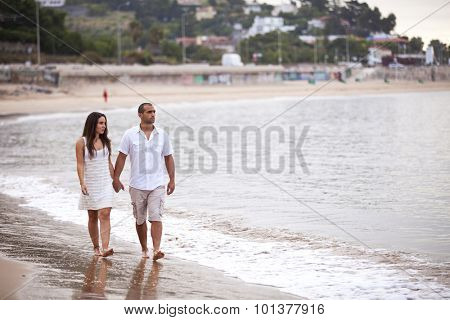 Couple holding hands and walking at the beach