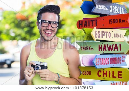 Hipster young guy with a vintage camera and geek glasses next to a signpost showing touristic destinations