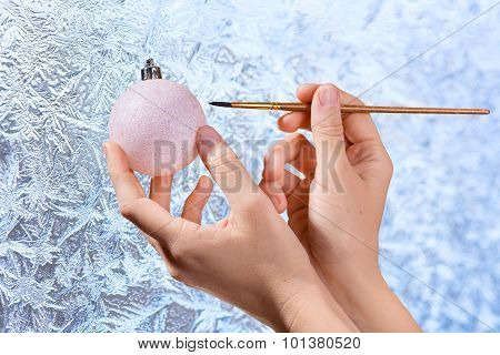 Women's Hands Drawing On Christmas Ball On Frosty Window Backgro