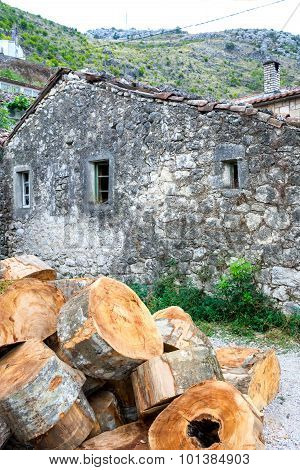 Stack Of Huge Sise Firewoods Prepared For The Cold Winter Near The Old Stone House In Montenegro.