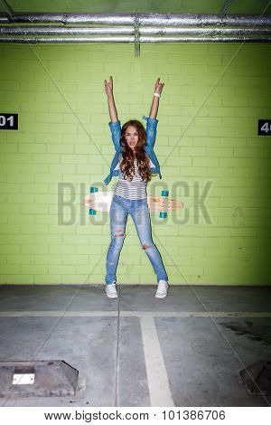 Beautiful Long-haired Girl With A Wooden Skateboard Near A Green Brick Wall