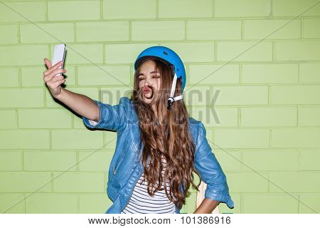 Beautiful Long-haired Woman With A Smartpnone Near A Green Brick Wall