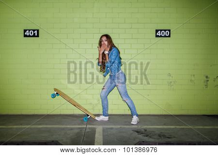 Beautiful Long-haired Woman With A Wooden Skateboard Near A Green Brick Wall