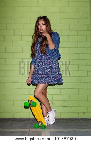 Beautiful Long-haired Girl With A Yellow Penny Skateboard Near A Green Brick Wall