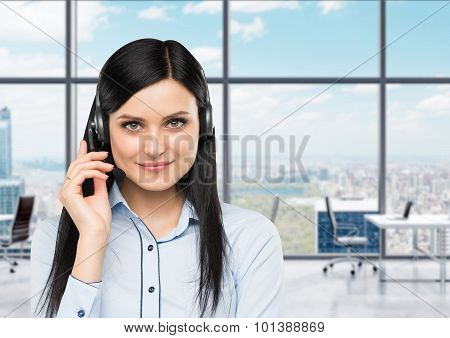 Front View Of The Smiling Brunette Support Phone Operator With Headset. Office Panoramic Office On T