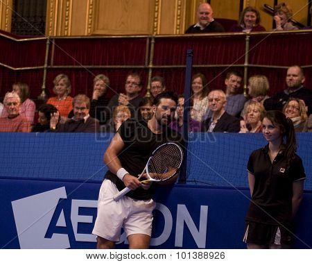 LONDON, ENGLAND. 06 DECEMBER 2009 -   Pat Rafter (AUS) takes a break and attempts to charm a ball girl whilst competing in the AEGON Masters Tennis, Royal Albert Hall, London.