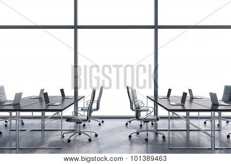 Workplaces In A Modern Panoramic Office, Copy Space In The Windows. Open Space. Black Tables And Bla