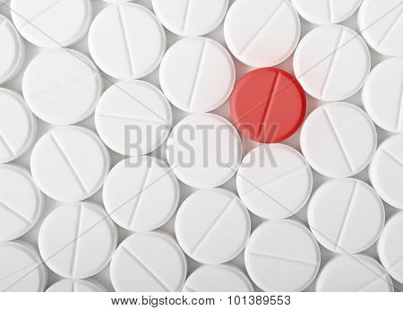 Top View Of The Heap Of White Medicine Pills On White Surface. One Red Medicine Tablet Is As A Conce