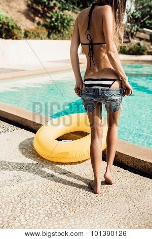 Beautiful Slim Girl In Sexy Striped Bikini Takes Off Her Shorts Near The Pool
