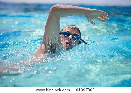 Young man swimming the front crawl/freestyle in a pool