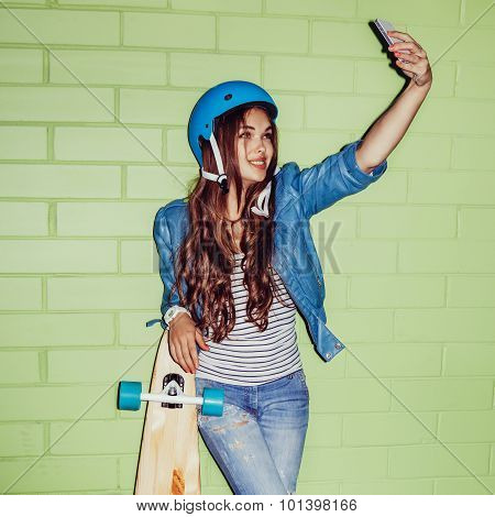 Beautiful Long-haired Girl With A Smartpnone Near A Green Brick Wall