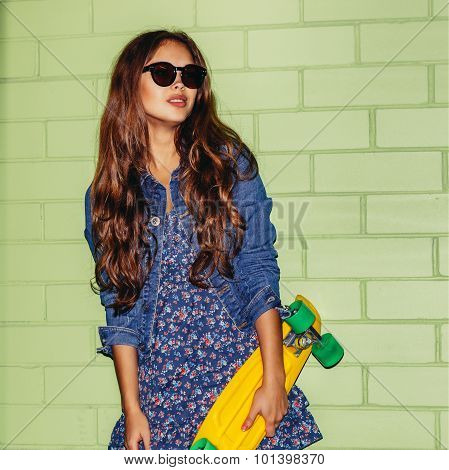 Beautiful Long-haired Woman With A Plastic Penny Board Near A Green Brick Wall