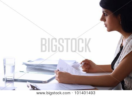 A young businesswoman looking frustrated while surrounded by paperwork