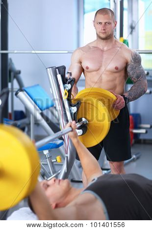 Shot of a young man performing bicep curls in a gym