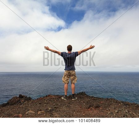 Freedom or nature lover concept - man with arms raised at seashore